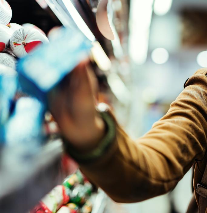 Immagine di una persona che sta acquistando un prodotto da uno scaffale del supermercato